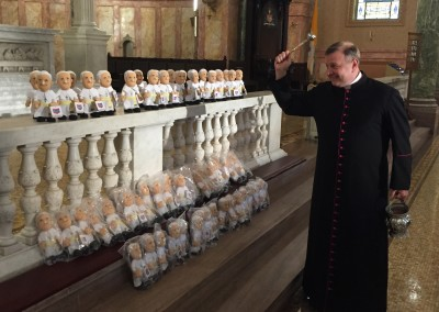 Msgr. Kieran Harrington blesses Pope dolls for CTN project